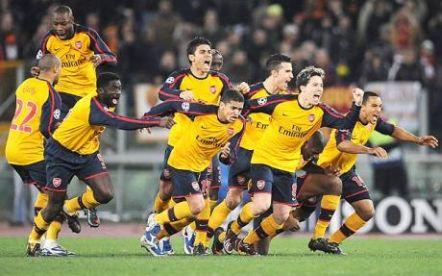 Arsenal players celebrate the winning penalty