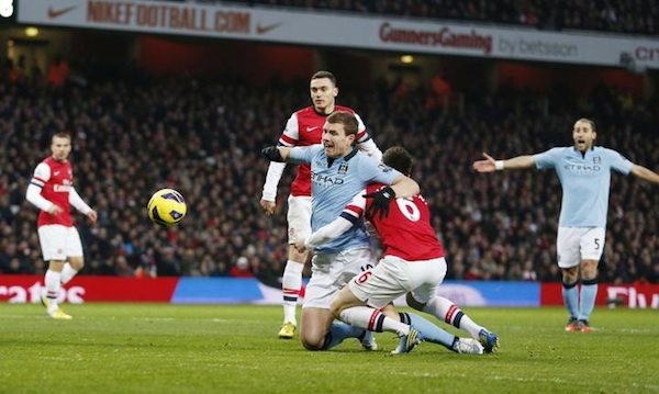 Laurent Koscielny wrestles Edin Dzeko to the ground